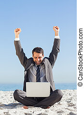 Victorious young businessman looking at his laptop -...