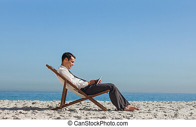 Young businessman resting on his deck chair using his tablet...