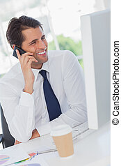 Smiling businessman on the phone looking at his computer