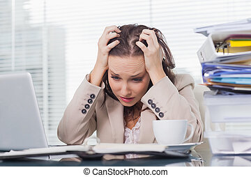 Nervous businesswoman pulling her hair out in her bright...