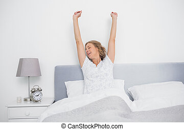 Well rested blonde woman stretching after waking up in bed...