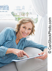 Happy blonde woman relaxing on her couch using her tablet...