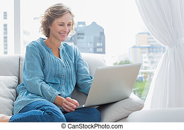 Cheerful blonde woman sitting on her couch using laptop at...