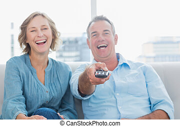 Laughing middle aged couple sitting on the couch watching tv...