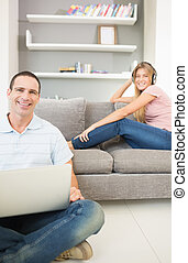 Man sitting on floor using laptop with woman listening to...