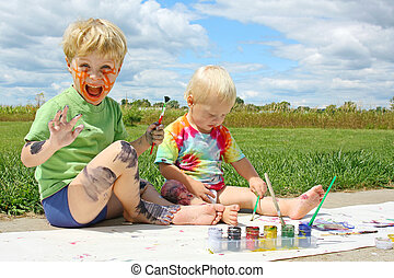 Messy Children Painting Outside - Two happy young children,...