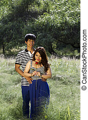 Vertical photo of young adult couple with woman looking at single red rose in the middle of a bright green grass field