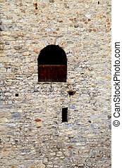 window in old stone wall of medieval castle - Arch window in...