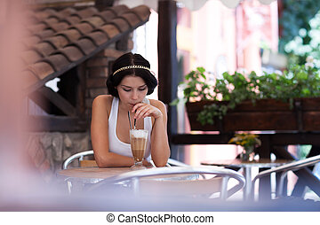 Young girl drinking cappuccino in a cafe - Portrait of...