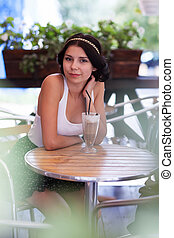 Attractive brunette girl in a cafe outdoors - Portrait of...