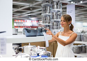 Pretty, young woman choosing a the right pot for her cooking...