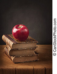 Stack of books and red apple