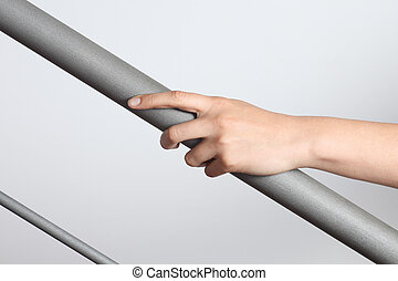 Woman hand using a railing to go upstairs with a light grey...