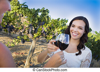 Young Woman Enjoying Glass of Wine in Vineyard With Friends...