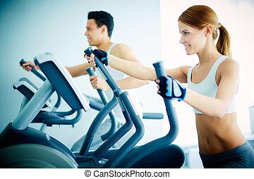 Training in health club - Portrait of pretty girl training...