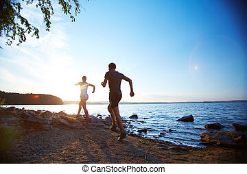 Running on the beach - Photo of young couple running on the...