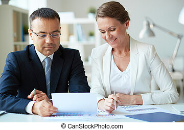Paperwork - Two mature business partners looking at document...
