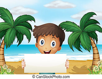 A boy at the beach holding an empty signage with a smile