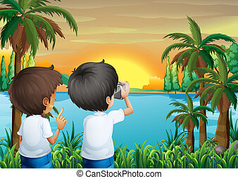 Two kids with a camera at the riverbank