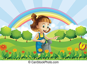 A young girl holding a sprinkler in the garden -...