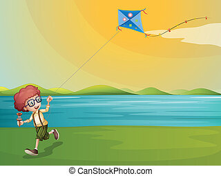 A young boy playing with his kite at the riverbank -...