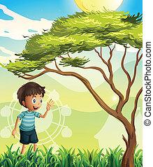 A happy boy near the tree