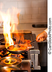 Chef cooking in kitchen stove - Chef cooking with flame in a...
