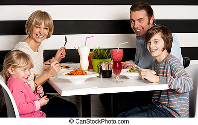 Family eating lunch together in restaurant - Father and...