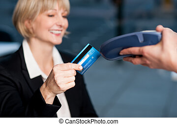 Corporate lady swiping her card to pay - Smiling senior...
