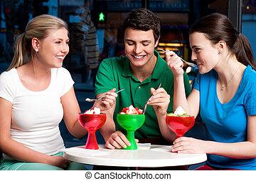 Three friends enjoying tempting dessert - Three friends...