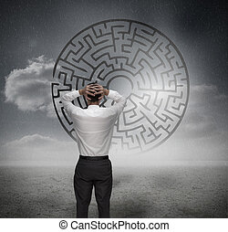 Anxious businessman looking at maze in dull grey landscape