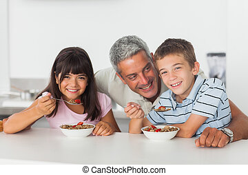 Happy father talking with his children during their...