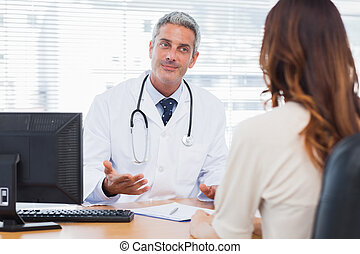 Smiling doctor talking with his patient in medical office