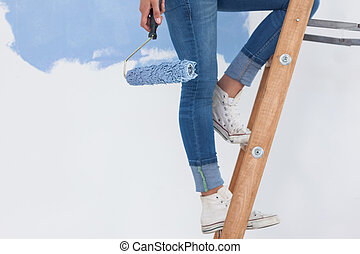 Woman holding paint roller on ladder against half painted...