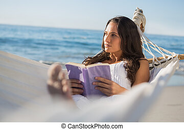 Woman lying on hammock holding book and thinking on the...