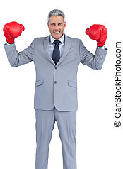 Businessman posing with red boxing gloves