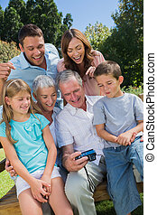 Multi generation family looking at photos on a park bench