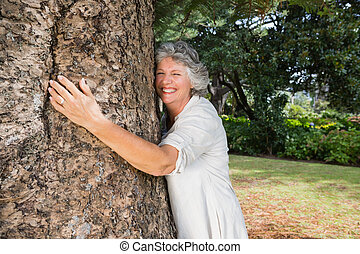 Smiling older woman hugging a tree in a park