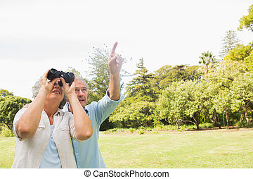 Man showing something to his wife with binoculars in the...