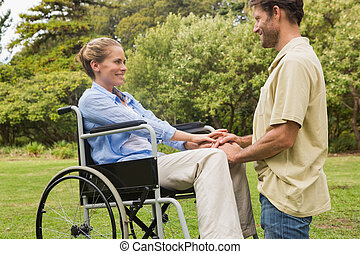 Attractive woman in wheelchair with partner kneeling beside...