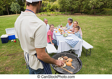 Father in chefs hat and apron cooking barbecue for his...