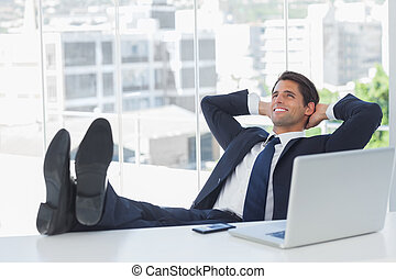 Successful businessman relaxing with his feet on his desk -...