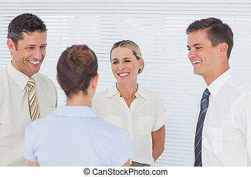 Smiling coworkers having a break together in staff room