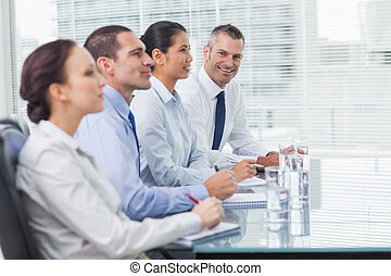 Businessman smiling at camera while his colleagues listening...
