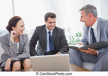 Business people laughing while having a meeting in cosy...