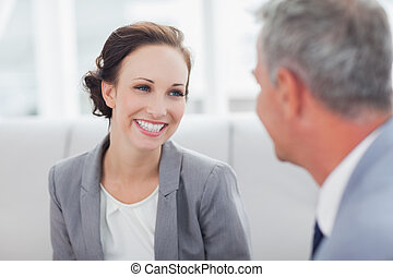 Cheerful businesswoman listening to her workmate talking in...
