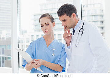 Focused surgeon and doctor working together in bright office