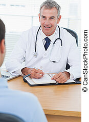 Cheerful doctor prescribing drug to his patient in bright...