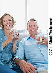 Happy middle aged couple sitting on the couch having coffee...