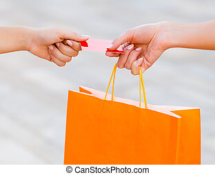 Paying with Card - Woman holding an orange bag and paying...